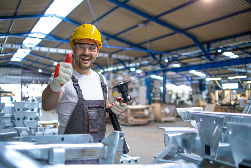 portrait-factory-worker-protective-equipment-holding-thumbs-up-production-hall